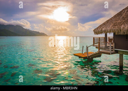 Evening with sunset in Moorea. Overwater bungalow on the side with breathtaking lagoon, French Polynesia - Stock Photo