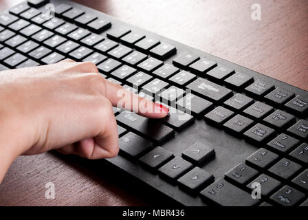 Girl finger push Enter button on computer keyboard on wooden desk. Close up - Stock Photo