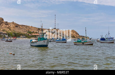 Heading out between the anchored Fishing Fleet of Wooden Boats moored just off Mancora Beach in Peru, South America. - Stock Photo