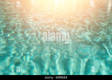 Close up abstract water texture. Turquoise swimming pool water background. Copy space, top view. Sun light effect and sunny bokeh. Summer, holiday and travel concept - Stock Photo