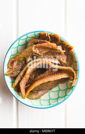Anchovy fillets in oil on wooden table. - Stock Photo
