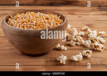 Raw corn seeds in bowl and popped popcorn on wooden desk - Stock Photo