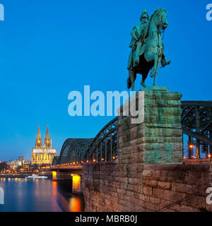 Equestrian statue of Emperor Wilhelm I. with Cologne Cathedral and Hohenzollern Bridge in the blue hour, Cologne, Rhineland - Stock Photo