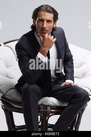 confident businessman sitting in chair - Stock Photo