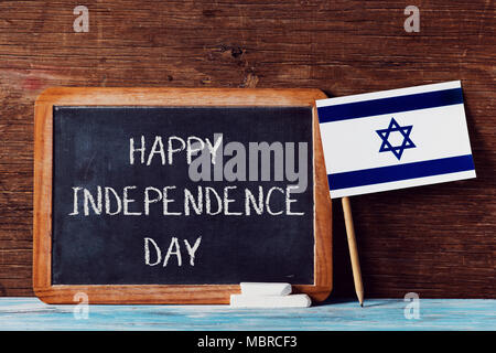 a wooden-framed chalkboard with the text happy independence day written in it, some pieces of chalk and an israeli flag on a rustic wooden surface - Stock Photo