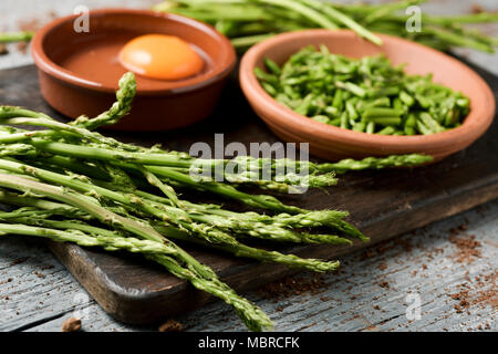 closeup of some wild asparagus and some earthenware bowls with chopped  asparagus and a cracked egg, the ingredients to prepare an asparagus omelet, o - Stock Photo