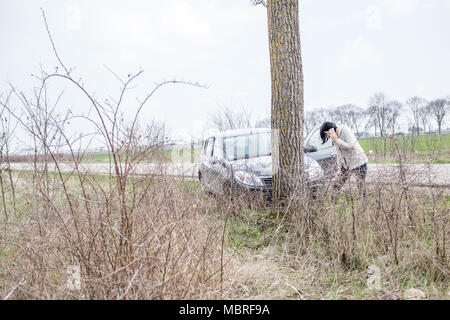 Stressed woman calling to car assistance after accident on the road - Stock Photo