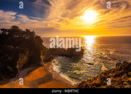 Sunset over McWay Falls on Pacific Coast Highway in California - Stock Photo