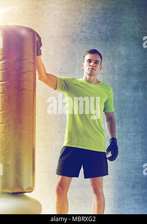 man with boxing gloves and punching bag in gym - Stock Photo