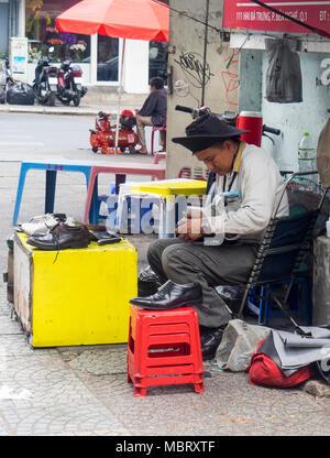 A male Vietnamese cobbler working on the sidewalk, repairing a shoe, Ho Chi Minh City, Vietnam. - Stock Photo