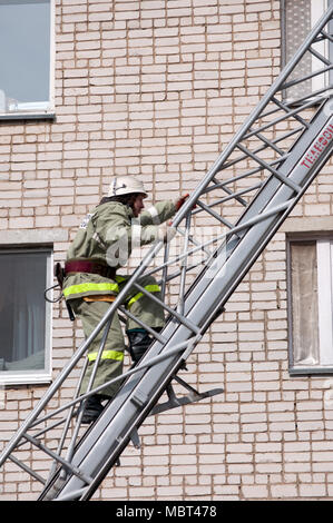 Yartsevo, Russia - August 26, 2011: The rescuer rises up the fire escape to a multi-storey building - Stock Photo