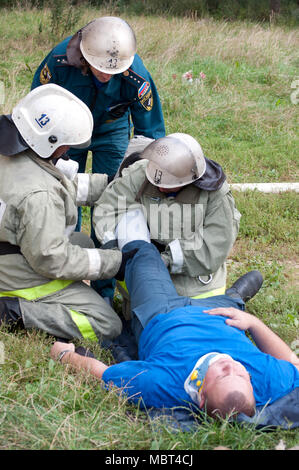 Yartsevo, Russia - August 26, 2011: Employees of the Ministry of Emergency Situations provide first aid to the victim - Stock Photo