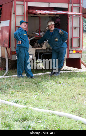 Yartsevo, Russia - August 26, 2011: Two firemen stand by the fire engine and look up - Stock Photo