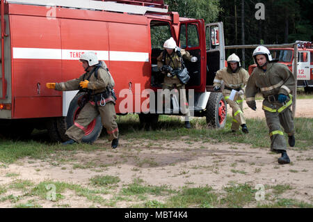 Yartsevo, Russia - August 26, 2011: Firefighters jump out and run from the cab of the fire truck - Stock Photo