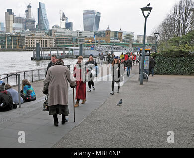 View of the financial district in The City of London & back view of elderly person with walking stick amidst tourists Bankside London UK  KATHY DEWITT - Stock Photo
