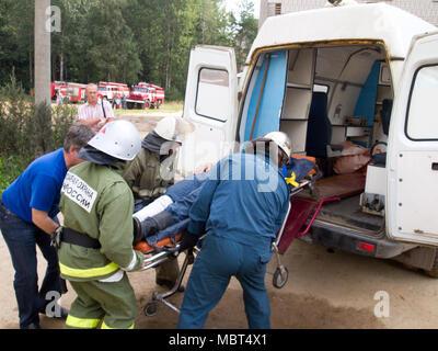 Yartsevo, Russia - August 26, 2011: EMERCOM employees load the victim in an ambulance - Stock Photo