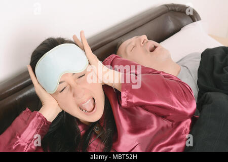 Portrait of irritated woman blocking ears with hands while man snoring on bed. Indoors - Stock Photo
