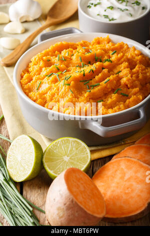Delicious puree of sweet potato with garlic and onion close-up in a bowl on the table. vertical - Stock Photo