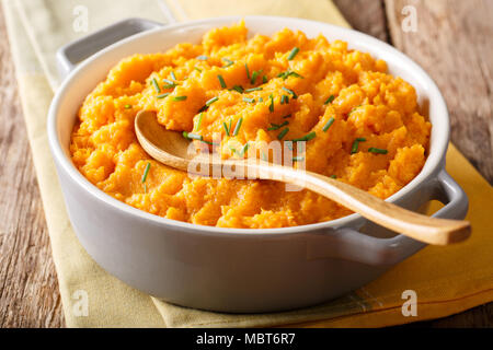 Vegetarian food: mashed sweet potatoes with herbs close-up in a saucepan on a table. horizontal - Stock Photo