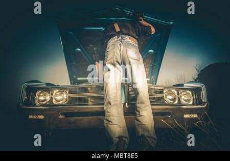 Fixing Broken Classic Car on the Side of the Countryside Road by Caucasian Men Wearing Western Style Clothes. Cowboy and His Vintage Ride. - Stock Photo