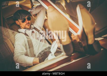 Caucasian Men in His 30s Western Wearing and Sunglasses Enjoying the Moment and in His American Classic Car Keeping His Legs on the Vehicle Door. - Stock Photo