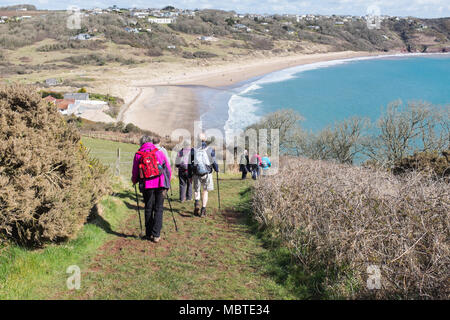 Group of walkers or ramblers descending a hill on the Pembrokeshire Coastal Path towards Freshwater East - Stock Photo