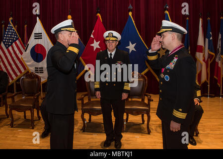 180111-N-TB148-170 Busan, Republic of Korea (Jan 11, 2018) - Rear Adm. Michael E. Boyle renders a salute to Rear Adm. Brad Cooper in front of Vice Adm. Phil J. Sawyer, commander, U.S. Seventh Fleet, assuming command of U.S. Naval Forces Korea (CNFK). During the ceremony Rear Adm. Michael E. Boyle relieved Rear Adm. Brad Cooper, becoming CNFK's 36th commander. (U.S. Navy photo by Mass Communication Specialist Seaman William Carlisle) - Stock Photo