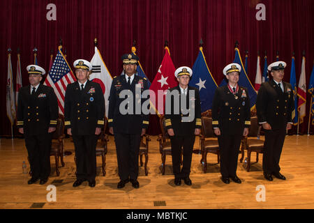 180111-N-TB148-044 Busan, Republic of Korea (Jan 11, 2018) - The official party stands at attention prior to the parading of the colors during a change of command ceremony at Commander, U.S. Naval Forces Korea headquarters. During the ceremony Rear Adm. Michael E. Boyle relieved Rear Adm. Brad Cooper, becoming CNFK's 36th commander. (U.S. Navy photo by Mass Communication Specialist Seaman William Carlisle/ Released) - Stock Photo