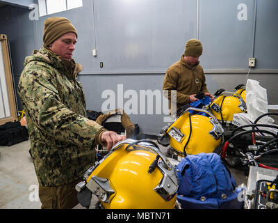 U.S. Navy Construction Mechanic 2nd Class Andersen Gardner and U.S. Navy Builder 2nd Class Aaron Brown, both assigned to Underwater Construction Team (UCT) 2, conduct maintenance on a KM-37 diving helmets during an underwater pile removal operation at Commander, Fleet Activities Sasebo (CFAS), Jan. 11, 2018. UCT-2 provides construction, inspection, maintenance, and repair of underwater and waterfront facilities in support of the Pacific Fleet. (U.S. Navy Combat Camera photo by Mass Communications Specialist 1st Class Arthurgwain L. Marquez) - Stock Photo