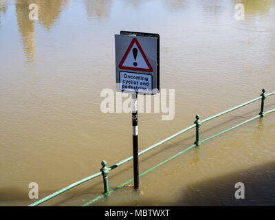 Red triangular road sign in high spring flood water level on track by River Severn. Shrewsbury, Shropshire, West Midlands, England, UK, Britain - Stock Photo
