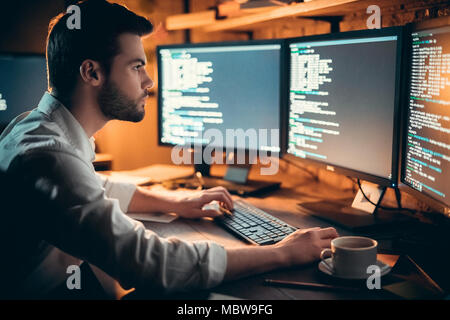 Focused young developer coding late in office writing script shown on computer monitors, serious handsome coder programmer hacker programming developi - Stock Photo