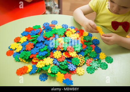 Close up image of child girl playing with block toys at table. - Stock Photo