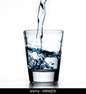 Small glass alcohol shot cup, being filled with blue water, or liquid, closeup, white background with reflection - Stock Photo