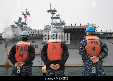 180114-N-RD713-046  SASEBO, Japan (Jan. 14, 2018) Sailors stand by to moor lines as the amphibious assault ship USS Wasp (LHD 1) arrives in Sasebo, Japan. The Wasp, capable of operating the U.S. Marine Corp's F-35B Joint Strike Fighter, will replace USS Bonhomme Richard (LHD 6) as the forward-deployed amphibious assault ship in 7th fleet area of operations. (U.S. Navy photo by Mass Communication Specialist 3rd Class Zachary DiPadova/Released) - Stock Photo