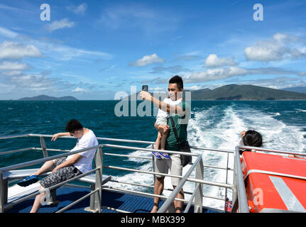 A young Chinese tourist taking a selfie while cruising at the Great Barrier Reef, Far North Queensland, QLD, FNQ, Australia - Stock Photo