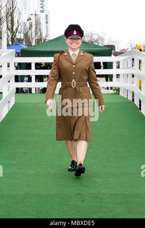 The Randox Health Grand National, Aintree, Liverpool, Merseyside. 12th April 2018.  Cheryl Hill of the Queens Own Regiment at the most famous event in the horse racing calendar welcomes people on this very special parade of Ladies outfits & the finest female fashions.  Racegoers have been urged to 'smarten up' to make the event more 'aspirational' as thousands of glamorous women pour through the entry gates on the one and only 'Grand National' as up to 90,000 visitors are expected to attend the spectacular National Hunt Racing event.   Credit: Mediaworld Images/Alamy Live News - Stock Photo