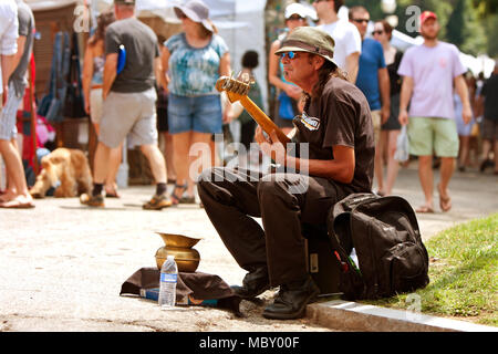 Atlanta, GA, USA - August 16, 2014:  A man plays bass guitar for tips while sitting on the curb at the Piedmont Park Arts Festival. - Stock Photo