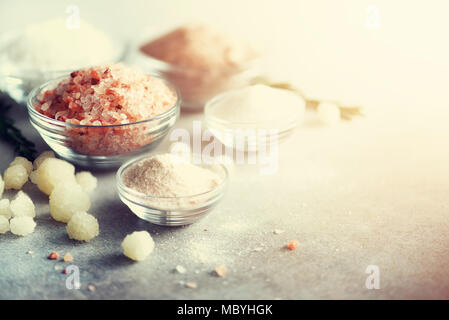 Mix of different salt types on grey concrete background. Sea salts, black and pink Himalayan salt crystals, powder, rosemary. Salt crystal balls from Dead sea. Copy space. Toned sunlight effect - Stock Photo