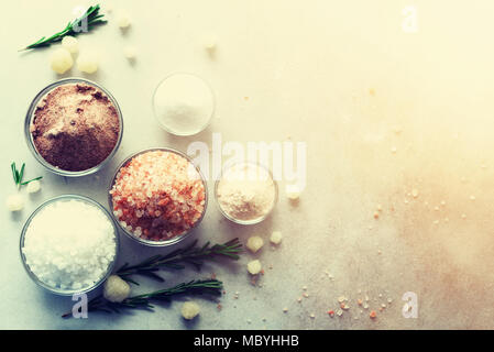 Mix of different salt types on grey concrete background. Sea salts, black and pink Himalayan salt crystals, powder, rosemary. Salt crystal balls from Dead sea. Copy space. Top view. - Stock Photo
