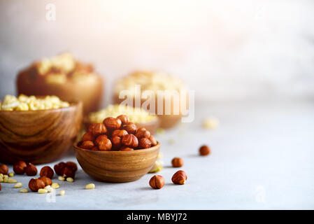 Hazelnuts in wooden bowl. Food mix background, top view, copy space, banner. Assortment of nuts - cashew, hazelnuts, walnuts, pistachio, pecans, pine nuts, peanut, raisins. - Stock Photo