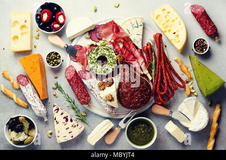 Cutting board with cold smoked meat, prosciutto, salami, assortment of cheeses, bread sticks, capers, olives on grey stone background. Cheese and meat appetizer. Top view, copy space, flat lay - Stock Photo