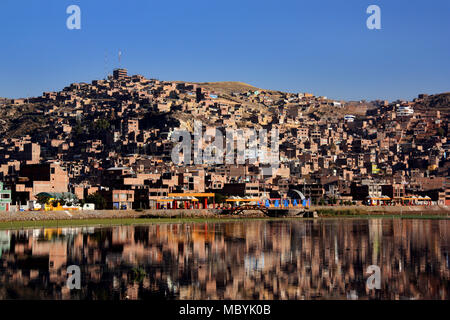 City of Puno reflecting on Lake Titicaca in Peru - Stock Photo