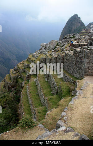Man sitting on the edge of a wall at the abandoned citadel of Machu Picchu high up in the Peruvian Andes and looking down into the valley - Stock Photo
