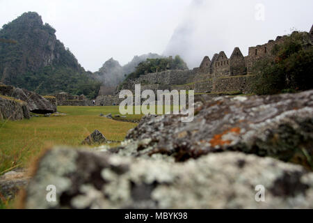 UNESCO World Heritage Site Machu Picchu on top of a Mountain Ridge above the Sacred Valley within the Rainforest in the Andes Mountain Range in Peru - Stock Photo