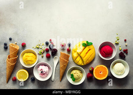 Ice cream balls in bowls, waffle cones, berries, orange, mango, pistachio on grey concrete background. Colorful collection, flat lay, summer concept, top view - Stock Photo