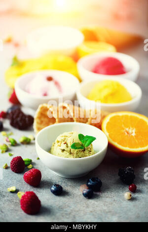 Ice cream balls in bowls, waffle cones, berries, orange, mango, pistachio on grey concrete background. Colorful collection, flat lay, summer concept - Stock Photo