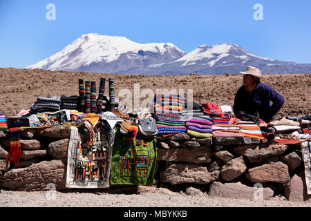 Peruvian Woman selling traditional Textiles on Top of a high Mountain Pass in the Andes - Stock Photo