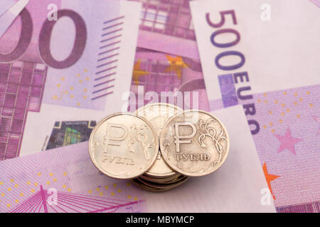 ruble coins and the symbol of the ruble and the numbers on Euro notes - Stock Photo