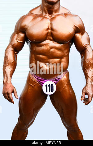 Young bodybuilder showing chest muscles in front pose Indian Body Builders Association show, Balewadi, Baner, Pune, Maharashtra India - Stock Photo