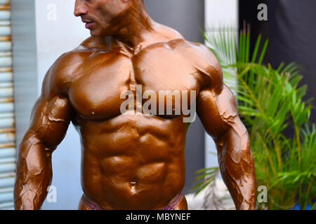 Young bodybuilder showing chest muscles in front pose Indian Body Builders Association show, Balewadi, Baner, Pune Maharashtra India - Stock Photo